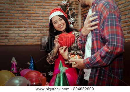 Young girl surprise gift heart to boyfriend couple together in christmas party with santa hat celebrate lover at home copy space the left