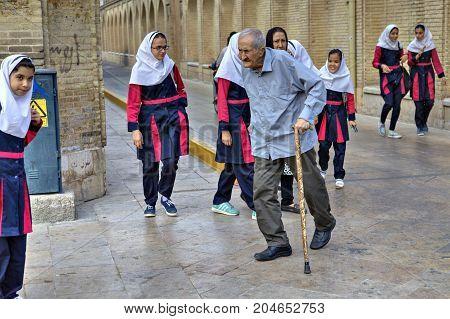 Fars Province Shiraz Iran - 18 april 2017: An elderly man with a cane walks past a group of girls in school uniform.