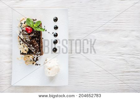 Chocolate pie on white plate with decoration from cherry, almond and mint. Delicious dessert serving in restaurant with ice-cream ball, top view with free space on background