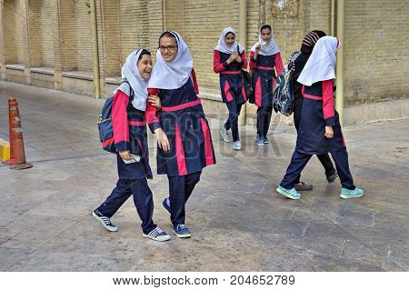 Fars Province Shiraz Iran - 18 april 2017: School girlfriends in school uniforms and hijabs return home after school.