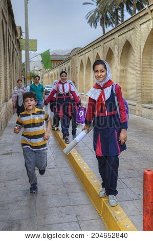 Fars Province Shiraz Iran - 18 april 2017: Iranian girl in school uniform goes home on a city street.