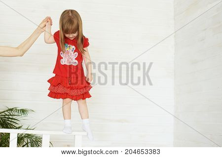 Young cute girl in red standing on railing.