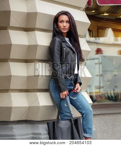 A fashionable girl with a black leather motorcycle jacket and ragged blue jeans stands near a fashion boutique and holds a black bag in her hands
