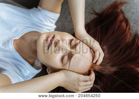 Dealing with pain. Sad cheerless young woman closing her eyes and holding her head while trying to deal with pain