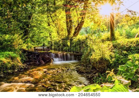 Sunlit river in a forest small natural waterfall. Clear mountain water