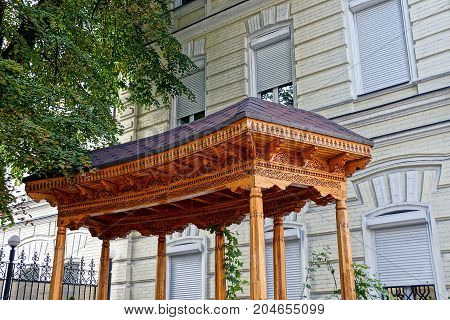 The roof of a wooden pergola near the wall of the house near the green tree