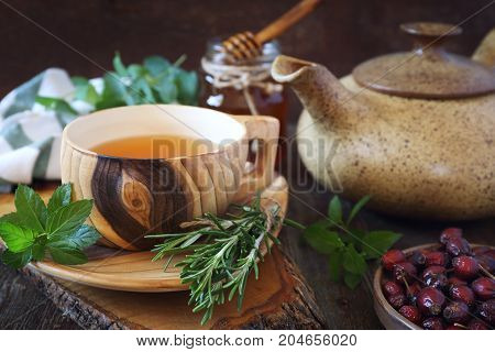 Healthy herbal tea with medicinal herbs rose hip and honey. Rustic style