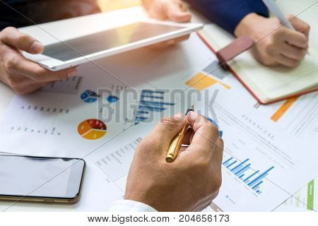 Business concepts,Businessman uses a pen pointing at graph,Office worker using a tablet and secretary is taking notes,smart phones and graphs on the desk.