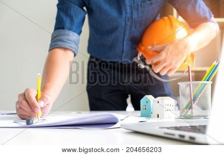Architects are using drawing pencils,On the other hand holds a safety hat,On the writing desk there are model houses laptop and house plans.