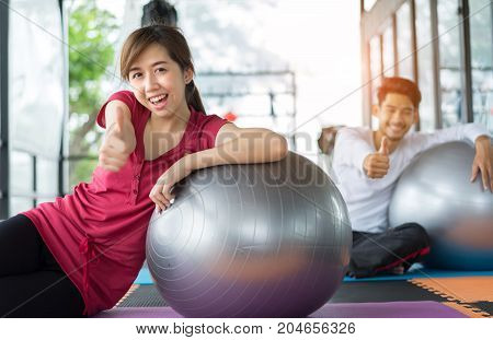 Young asian woman and man fitness exercise aerobics with yoga ball indoor for building muscle slim body and strong perfect