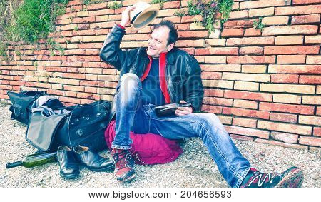 Homeless drunk man greets the day smiling with funny gesturing - Clochart sitting at city park holding wine bottle with cheerful attitude - Concept of alcohol addiction and social discomfort