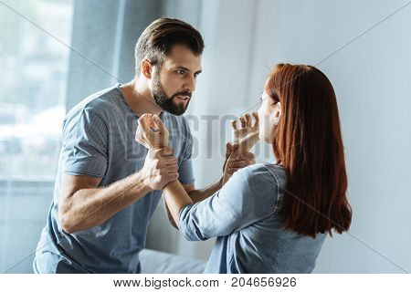 Home violence. Furious cheerless brutal man looking at his wife and holding her arms while being angry at her