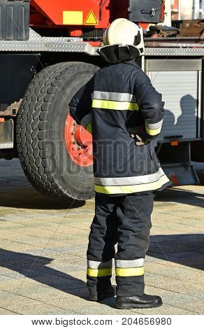 Firefighter stands next to a vehicle outdoor