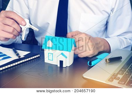 Man giving keys from house in a real estate agency.