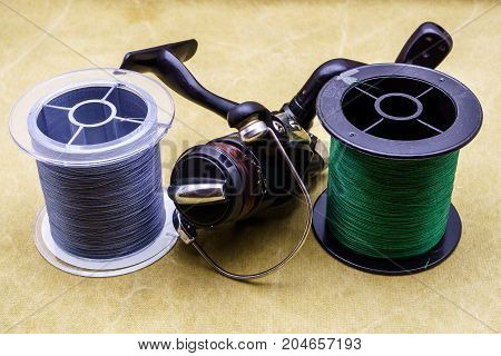 Fishing Reel And Spools Of Cords On The Background Of Tarpaulin. Green And Gray Fishing Line. Spools