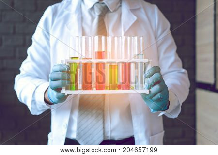 Scientist man with glasses working reserch and conducts experiments by synthesising compounds in laboratory and the test tube