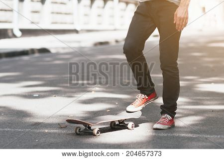Unrecognizable hipster man with skateboard. First step in skateboarding sport challenge, ready to adventure. Modern urban lifestyle and culture of youth background with free space