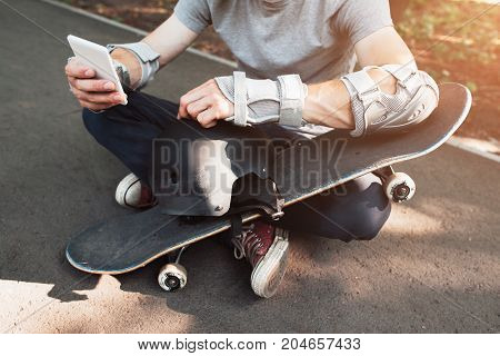 Skateboarder has short break in online network. Extreme sport challenge combining with active social life, internet and mobile phones in sportive urban lifestyle and culture of young people