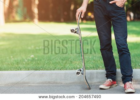 Unrecognizable man with skateboard in hands. Extreme sport challenge and competition, readiness for adventure and self-confidence. Skateboarding background with free space, urban lifestyle and culture