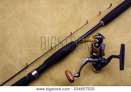 Spinning Rod With Fishing Reel On The Background Of Tarpaulin. Fishing Tackle On The Background Of T