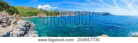 BUDVA MONTENEGRO - SEPTEMBER 7 2017: Unknown people admire panoramic view of Budva coast (Mogren beach Budva Old Town Sveti Nikola Island) from high cliff near beach Montenegro