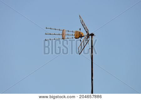image of TV antenna against the blue sky