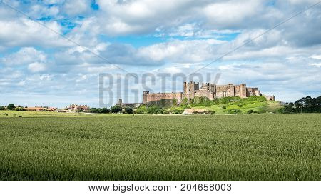 Bamburgh village and Castle, England. A view over the Northumberland countryside in north-east England towards the village of Bamburgh dominated by its famous landmark castle.