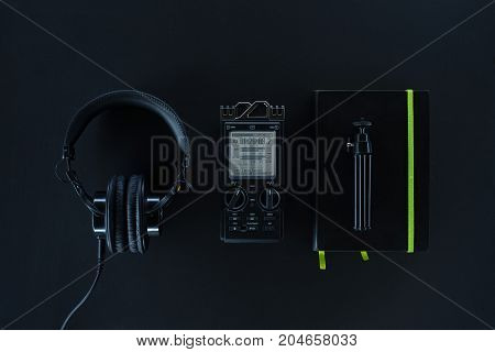 Compisition with field audio recorder headphones and notebook on the dark background