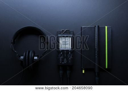 Compisition with field audio recorder headphones notebook and shotgun microphone on the dark background