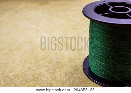 Spool Of Cord On The Background Of Tarpaulin. Green Fishing Line. Spool Of Braided Fishing Line