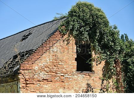 Ruined old house wall and roof against sky