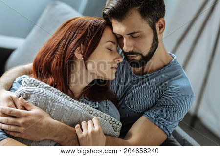 Pleasant feeling. Calm peaceful loving couple sitting together and closing their eyes while resting