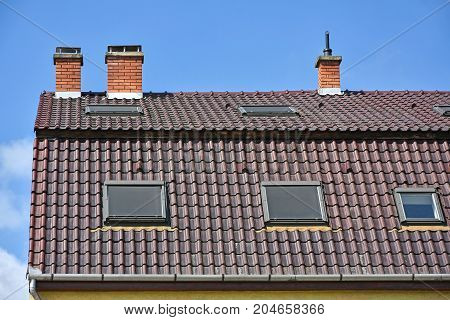 House roof with smoke stacks against blue sky