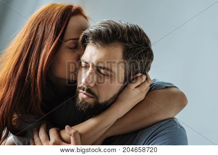 Wonderful moment. Delighted calm peaceful man sitting together with his girlfriend and closing his eyes while feeling her kiss