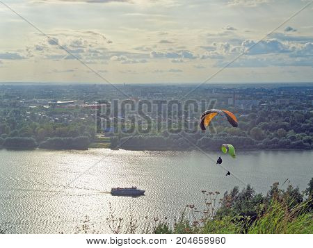 Two paragliders fly over the river against the background of the evening sky. A ship is sailing along the river. In the distance can be seen an industrial city