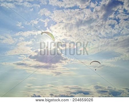 Two paragliders fly against the background of the evening sky. The rays of the sun make their way through the clouds