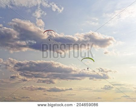 Two paragliders fly against the background of the evening sky with clouds