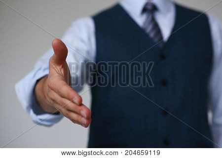 Man In Suit And Tie Give Hand As Hello In Office