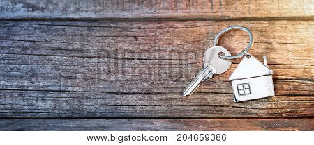 House Key And Keychain On Wooden Table