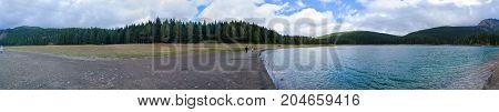 ZABLJAK MONTENEGRO - SEPTEMBER 12 2017: Unknown people walk along shore of Black Lake in cloudy September day Durmitor National Park Montenegro