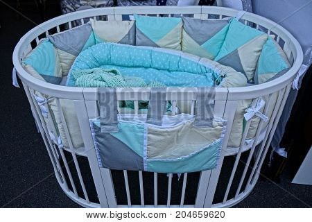 small baby cot with blanket and pillow in the room