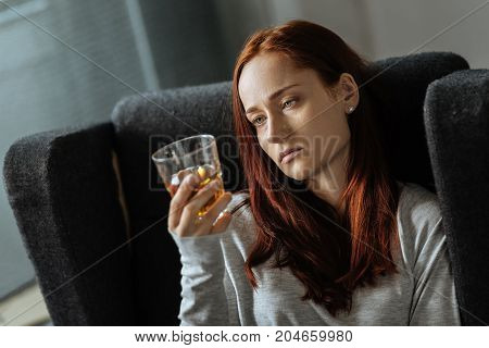 Alcohol addiction. Pleasant sad unhappy woman holding a glass of whisky and drinking it while being alcohol addicted