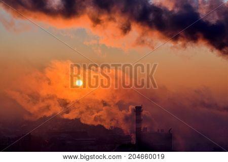Smoking smoke stack at sunrise in backlight