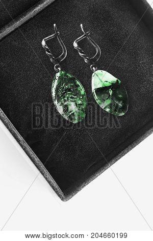 Elegant malachite earrings in black jewel box closeup