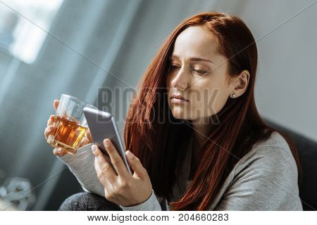 Alcoholic drink. Pleasant sad cheerless woman holding a glass of whisky and using her smartphone while feeling upset