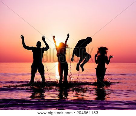Silhouettes of happy friends jumping inside water on the beach at sunset - Group of young people having fun on summer vacation - Youth and friendship concept - Focus on bodies silhouette