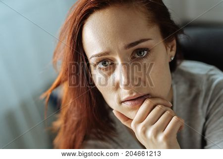 Depressing thoughts. Portrait of a beautiful nice thoughtful woman holding her chin and having depressing thoughts while looking at you