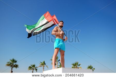 Man holding two UAE flags against the blue sky Celebration of National Day - Day of the United Arab Emirates concept