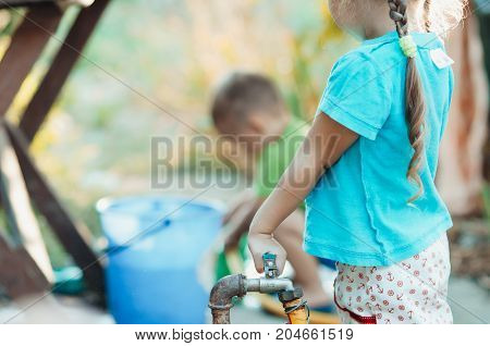 Kids play water girl in front overlaps the tap water