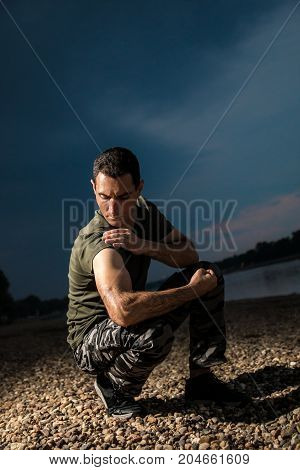 Handsome man in military style demonstrate his muscles and biceps seating on rocky beach dramatic look
